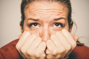 worried woman with hands pressed to her face