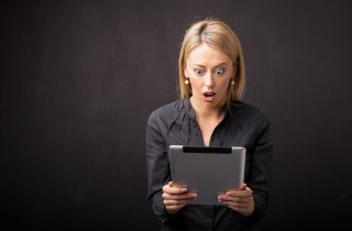 shocked woman staring at tablet
