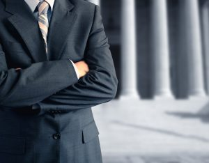 suited man with arms crossed in front of courthouse