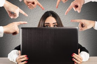 woman behind computer screen with fingers pointing at her