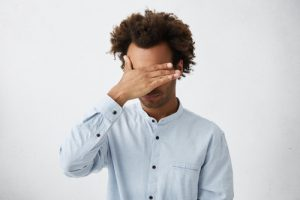Black man with hand over his face