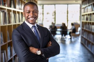 Smiling African American lawyer crossing arms with meeting behind him
