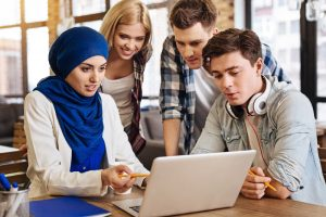 colleagues gathered around laptop with a woman with hijab